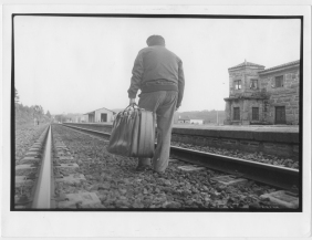 Migrants with her suitcase walking down the railroad tracks. Photographer: Xurxo Lobato