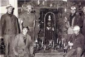 The picture shows a group of Italian miners with work overalls in the mine of Volmèrange-les-mines (France), next to Saint Barbara's statue (patron and protector of miners) during her celebrations. France, 1953.