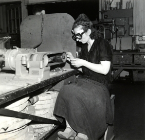 An italian worker near some machinery for the fabrication of metal parts, 1950 ca.
