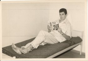 30th November 1963. Reading a book at bed (to note the written Volkswagen on the blanket)