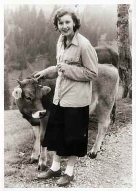 Santi Lina close to a cow in the mountains around Zug.1956-1957